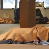People lie on the floor under blankets at New Chitose Airport on Monday morning after their flights on Saturday and Sunday were canceled due to heavy snow. | KYODO