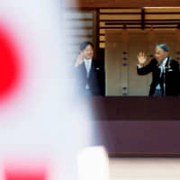 Emperor Akihito and Crown Prince Naruhito are seen behind Hinomaru flags as they wave to well-wishers during New Year's celebrations at the Imperial Palace in Tokyo on Jan. 2. | REUTERS