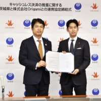 Ibaraki Gov. Kazuhiro Oikawa (left) and Yoshiki Yasui, president of Tokyo-based QR-code payment service provider Origami Inc., display their agreement to the media at a signing ceremony Wednesday at the Ibaraki Prefectural Government office in Mito. | KYODO