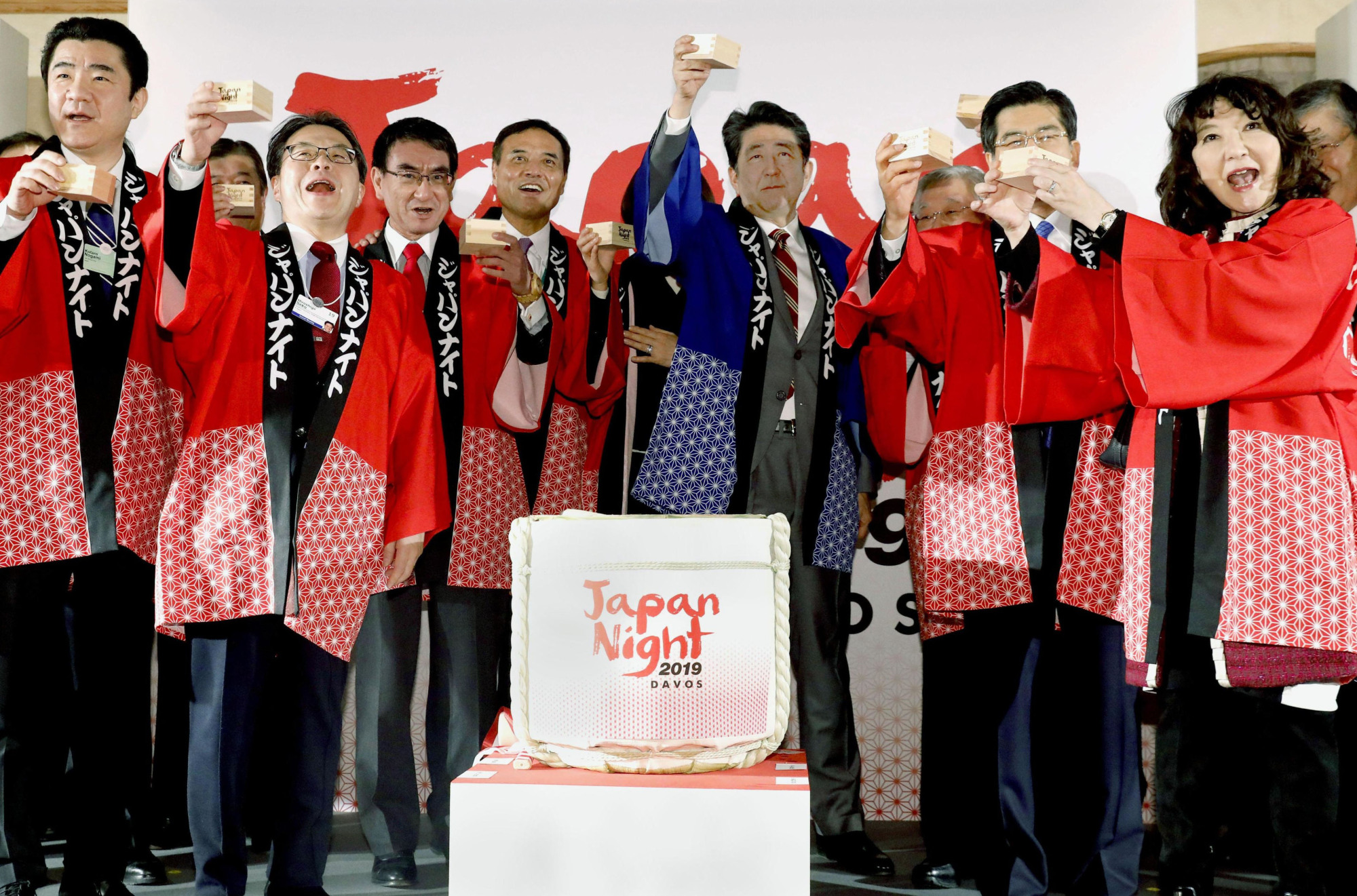 Prime Minister Shinzo Abe and other Japanese officials toast with sake produced in Fukushima Prefecture during the Japan Night event in Davos, Switzerland, on Wednesday. | KYODO