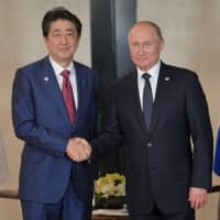 Prime Minister Shinzo Abe and Russian President Vladimir Putin attend a meeting on the sidelines of the ASEAN-Russia Summit in Singapore last November. | REUTERS