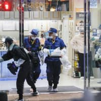 Police search a karaoke bar in the Kabukicho entertainment district in Shinjuku Ward, Tokyo, following a shooting there Monday evening. | KYODO