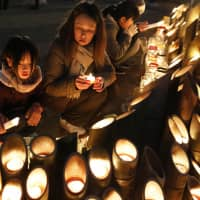 People light candles in Kobe on Thursday, the 24th anniversary of the Great Hanshin Earthquake, which killed more than 6,000 people in the city and its vicinity. City officials vowed to pass on the lessons from the disaster. | KYODO