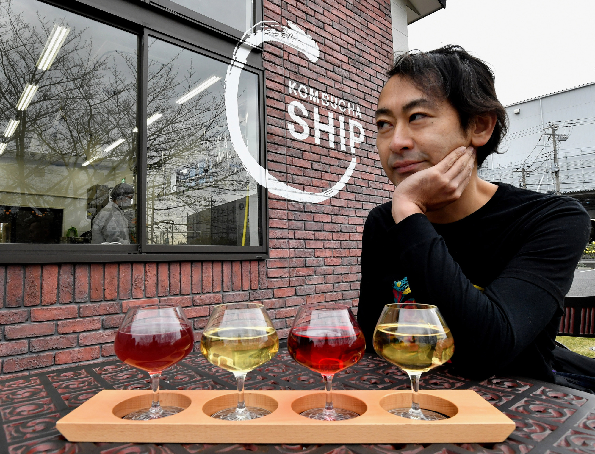 Kantaro Oizumi, president and CEO of Oizumi Kojo, sits outside his kombucha brewery. Captivated by the health drink, Oizumi decided to launch Japan's first full-scale kombucha brewery in 2016 with the help of brewer Yuji Shimada.