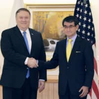 Foreign Minister Taro Kono (right) and U.S. Secretary of State Mike Pompeo (left) shake hands in Tokyo on Oct. 6. They agreed Monday to meet again in mid-February. | POOL / VIA KYODO