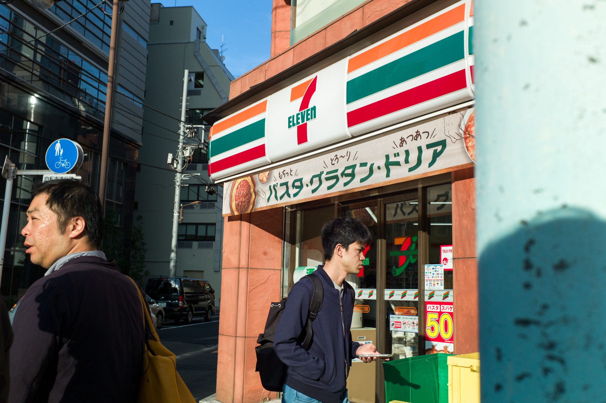 Pedestrians walk past a Seven-Eleven convenience store in Tokyo, operated by Seven & I Holdings Co., in October 2017. Japan's three largest convenience store operators now plan to stop selling pornographic magazines by the end of August. | BLOOMBERG