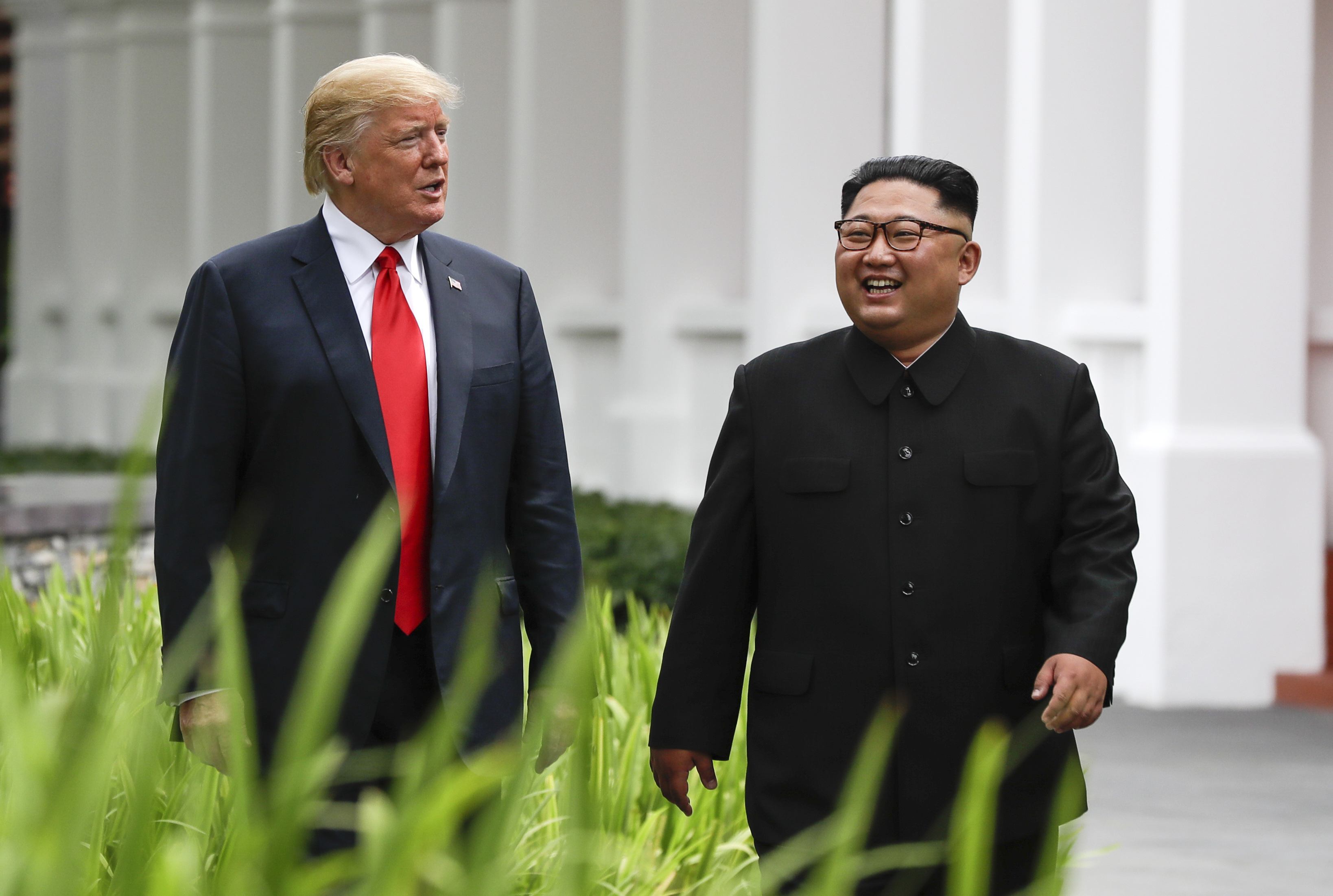 U.S. President Donald Trump and North Korean leader Kim Jong Un walk from their lunch at the Capella resort on Sentosa Island in Singapore last June.  | AP