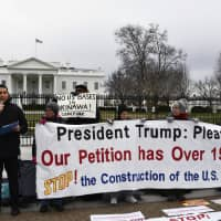 Robert Kajiwara and others call for a halt to construction of a U.S. base in Okinawa during a rally in front of the White House in Washington on Monday. | KYODO