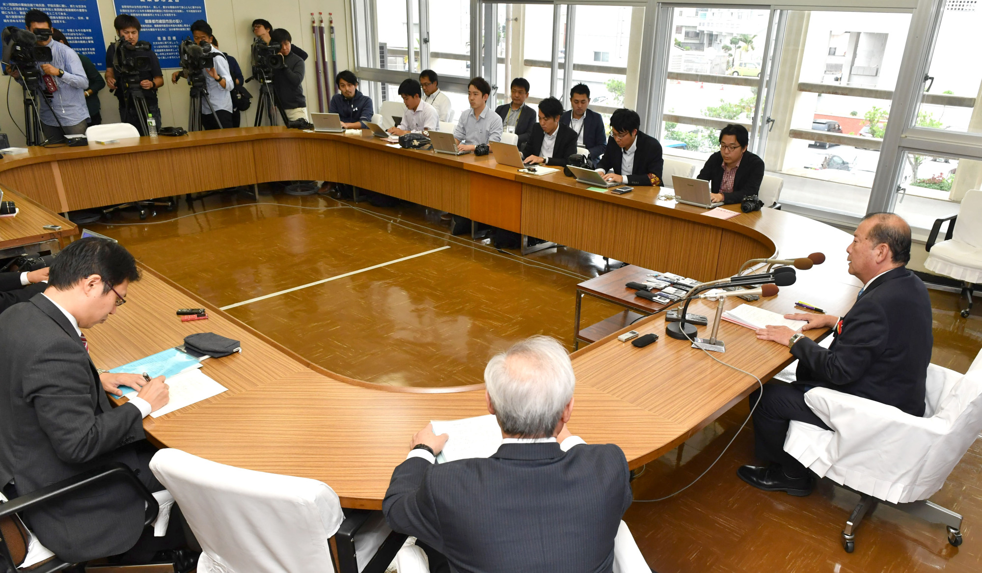 Ginowan Mayor Masanori Matsugawa (far right) announces his decision that a prefectural referendum will not be held in the city, at the Ginowan municipal office on Dec. 25. | THE OKINAWA TIMES