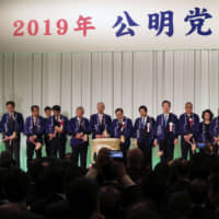 Komeito leader Natsuo Yamaguchi and members of the party's Osaka headquarters hold a New Year's party Wednesday in the city of Osaka. In a break with tradition, Osaka Gov. Ichiro Matsui and other Osaka Ishin no Kai leaders were absent, due to a rift over a plan to merge Osaka city into four semiautonomous wards. | KYODO
