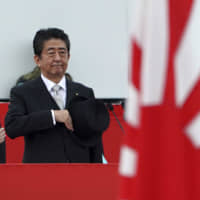 Prime Minister Shinzo Abe reviews members of the Self-Defense Forces at a base just north of Tokyo on Oct. 14. Political observers say Abe may engineer a double election in summer this year by dissolving the Lower House to coincide with the pre-scheduled July Upper House poll. | AP