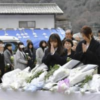 During a ceremony held in Hiroshima on Sunday to mark six months since the disaster, people mourn victims who died after heavy rain hit parts of western Japan last July. | KYODO