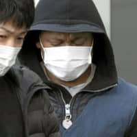 A suspect arrested in a case involving an online romance scam is taken to Fukuoka Prefecture on Tuesday. | KYODO