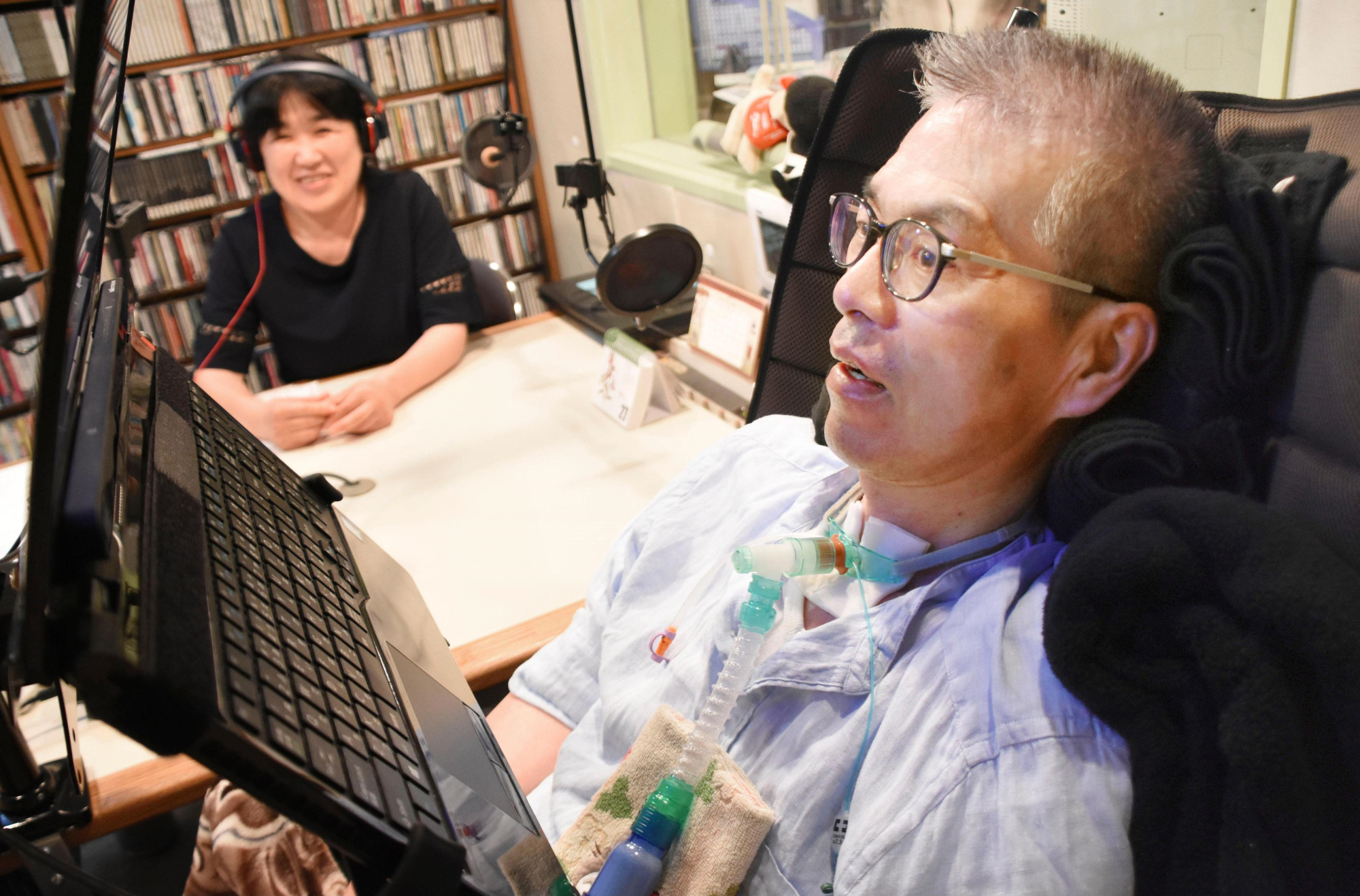 Kazuya Yoneza, who is unable to speak because of Lou Gehrig's disease, hosts a radio program by using the Voistar voice-synthesis software last July in Sapporo. | KYODO