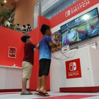 Children play a game on a Switch console at the Nintendo Check In game experience area of Terminal 1 at Kansai International Airport in Izumisano, Osaka Prefecture, last July. | BLOOMBERG
