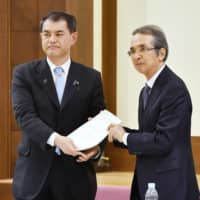 Teisuke Kitayama (right), head of the Central Council for Education, hands proposals to reduce teachers' overtime work to education minister Masahiko Shibayama in Tokyo on Friday. | KYODO