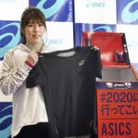 Saori Yoshida, a three-time Olympic wrestling champion, holds up a T-shirt she wore at the 2016 Rio de Janeiro Games. Yoshida is donating the shirt to a project launched Thursday by Asics Corp. to make uniforms for the Japanese Olympic and Paralympic teams by recycling sportswear items. | KYODO