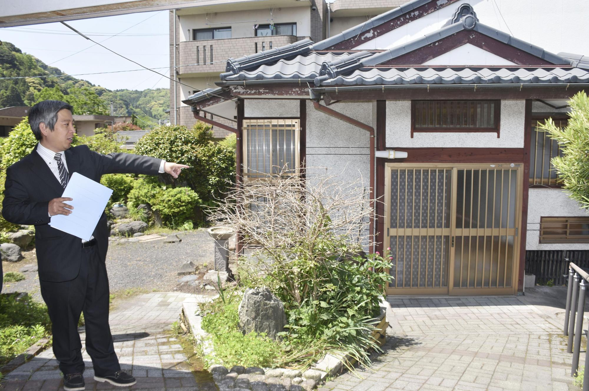 A consultant dispatched by the Kagoshima Municipal Government to advise on the reuse of vacant houses points is seen an empty home in the city in April. | KYODO