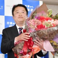 Kotaro Nagasaki holds a bouquet of flowers Sunday after winning the gubernatorial election in Yamanashi Prefecture. | KYODO