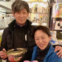 Takayoshi Igarashi and his wife, Takami, pose for a photo with household items from their shop, Igarashi Kanamonoten. | KIT NAGAMURA