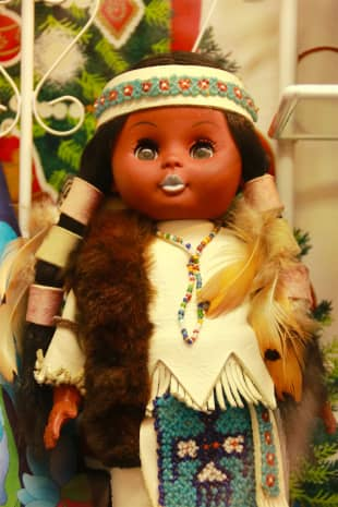 A doll dressed in Native American clothing sits in a hosiery shop called Indian in the arcade.