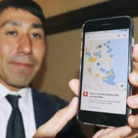 Find your way: A smartphone displays an online map that shows  hot spring locations that are OK with customers who have tattoos. | KYODO