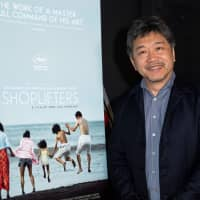 'Tis the season: Hirokazu Kore-eda stands next to a poster for his film, 'Shoplifters,' at the Golden Globe Foreign Language Symposium in Hollywood on Jan. 5. | AFP-JIJI