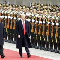 U.S. President Donald Trump reviews an honor guard with Chinese President Xi Jinping in 2017. The rise of China presents America with its greatest challenge since the Cold War. | BLOOMBERG