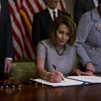 U.S. House Speaker Nancy Pelosi, a Democrat from California, signs a deal to end a partial government shutdown at the U.S. Capitol in Washington on  Jan. 25. | BLOOMBERG