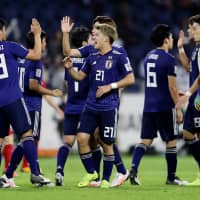 Ritsu Doan (center) and his Samurai Blue teammates celebrate their 1-0 win over Vietnam in the Asian Cup quarterfinals on Thursday night at Al-Maktoum Stadium in Dubai, United Arab Emirates. | REUTERS