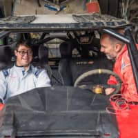 Jacques Barron (right) and his son and co-driver Lucas Barron are seen in December in Lima, where their car is being prepared to take part in the upcoming Dakar Rally. | AFP-JIJI