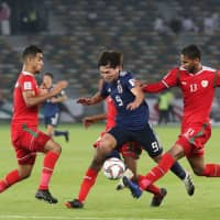 Japan's Takumi Minamino (center) fights for the ball in the middle of a group of Omani players during the Asian Cup on Sunday in Abu Dhabi. Japan won 1-0 to advance to the knockout phase of the tournament. | AFP-JIJI