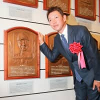 Former Chunichi Dragons infielder Kazuyoshi Tatsunami stands next to a plaque of the late Senichi Hoshino at Tuesday's Japanese Baseball Hall of Fame announcement event in Tokyo. | KAZ NAGATSUKA