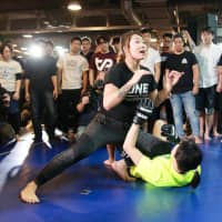 ONE Championship atomweight champion Angela Lee demonstrates a hold during the seminar in Tokyo. | KAZ NAGATSUKA