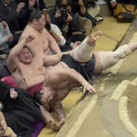 Ringside seats are popular among sumo fans despite the danger of wrestlers occasionally falling out of the raised ring.   KYODO