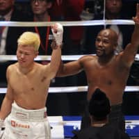 Mayweather lifts Nasukawa's arm and waves to the crowd following the bout, which Mayweather won via technical knockout.   AP