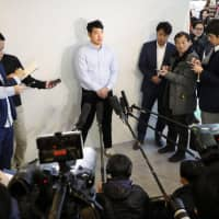 Seattle Mariners pitcher Yusei Kikuchi speaks to the media after arriving at Narita Airport on Sunday. | KYODO