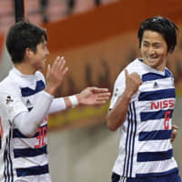 F. Marinos midfielder Kosuke Nakamachi (right) celebrates after scoring a goal against Albirex in Levain Cup action on April 4 in Niigata. The 33-year-old announced his plans to join a club in Zambia on Wednesday. | KYODO