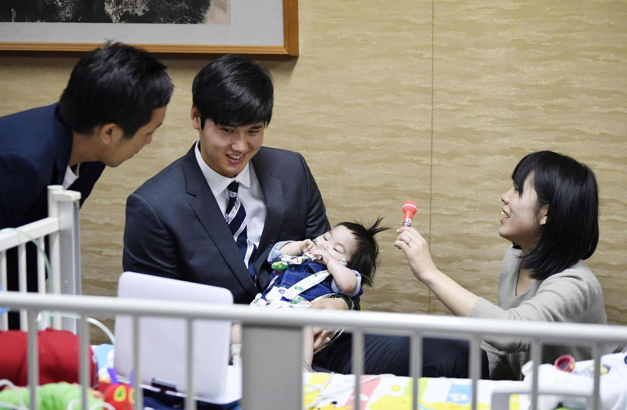 Shohei Ohtani (center) holds one-year-old Shohei Kawasaki at an Osaka Prefecture hospital on Saturday. Kawasaki's parents, who named him after the Los Angeles Angels star, are calling for donations in order to cover the cost of his heart transplant in the United States. | KYODO
