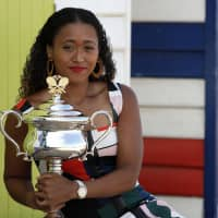 Japan's Naomi Osaka holds the Daphne Akhurst Memorial Cup at Melbourne's Brighton Beach on Sunday, following her win over Petra Kvitova of the Czech Republic in the women's singles final at the Australian Open tennis championships in Melbourne, Australia. | AP