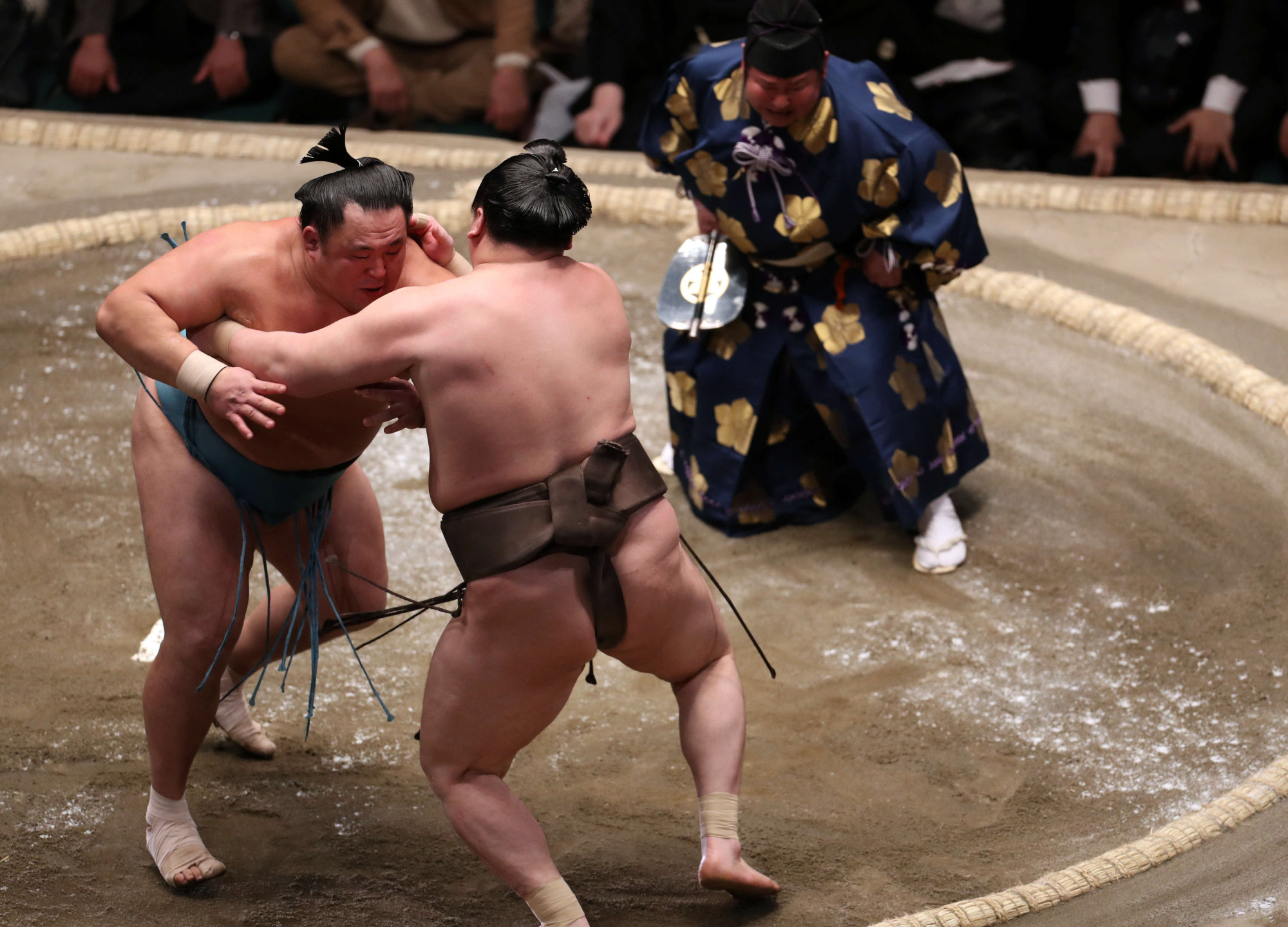 Sekiwake Tamawashi (left) forces out Hakuho to hand the yokozuna his second loss of the New Year Grand Sumo Tournament on Thursday at Ryogoku Kokugikan. They are tied at 10-2 with three days remaining at the 15-day tourney. | NIKKAN SPORTS
