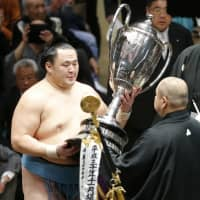 Sekiwake Tamawashi (left) receives the trophy from JSA chairman Hakkaku on Sunday at Ryogoku Kokugikan. | NIKKAN SPORTS
