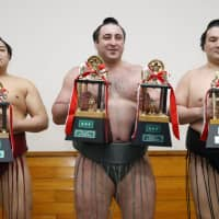 Fighting Spirit Prize winner Abi (left), Technique Prize and Outstanding Performance Prize recipient Tochinoshin (center) and Fighting Spirit Prize winner Ryuden pose with their awards after last year's New Year Basho on Jan. 28, 2018. | KYODO