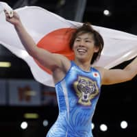Saori Yoshida wins her third Olympic medal in the women's 55-kg freestyle wrestling competition in London on Aug. 9, 2012. | AP