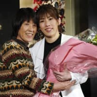 Three-time Olympic wrestling gold medalist Saori Yoshida (right) and her mother, Yukiyo Yoshida, pose for photographers on Thursday after she made her retirement announcement. | AP