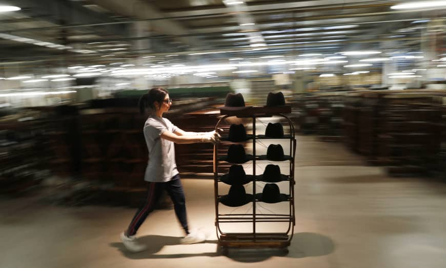 A woman worker pushes a cart with hats in Borsalino's hat factory, in Spinetta Marengo, near Alessandria, Italy, Jan. 17. | AP