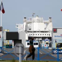 A migrant walks near the gates of the Brittany ferry port in Ouistreham, northwestern France, in September. As Brexit approaches, the ports of the English Channel and the North Sea are preparing for the worst, as they do not know what to expect beyond March 29 both in terms of customs controls and the evolution of traffic. | AFP-JIJI
