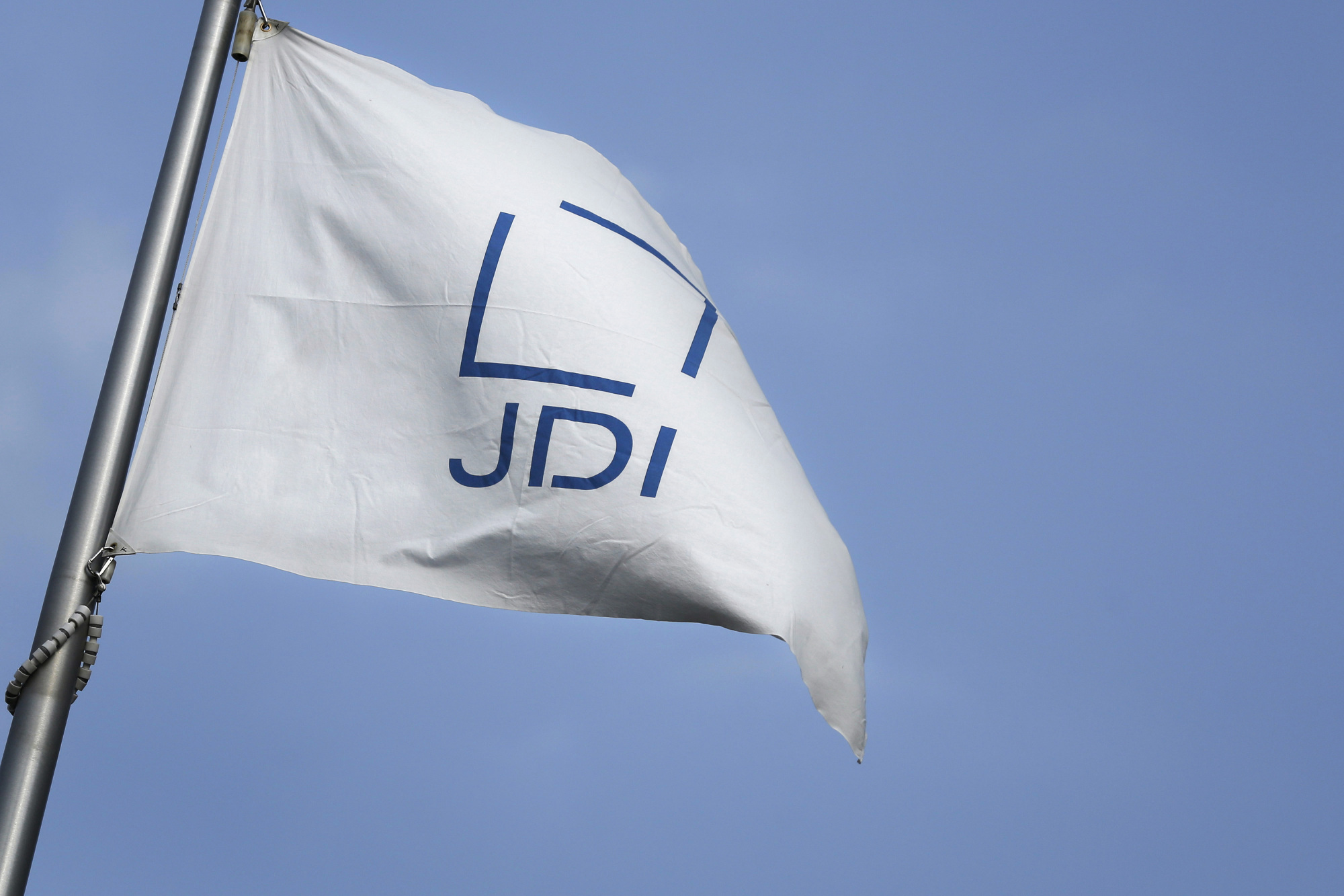 The Japan Display Inc. corporate flag files outside the company's plant in Mobara, Chiba Prefecture. | BLOOMBERG