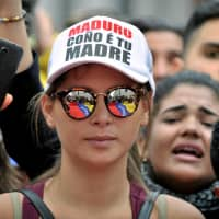 A demonstrator takes part in a protest against Venezuelan President Nicolas Maduro as a meeting of the Lima Group takes place in Bogota Monday. The baseball cap reads 'Maduro Son of a Bitch.' | REUTERS