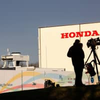 Members of media stand outside the Honda car plant in Swindon, western England, on Monday.   REUTERS